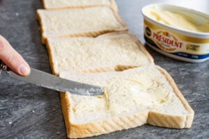 Spreading butter with a knife on four slices of white bread