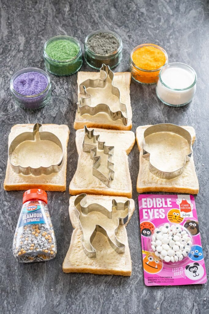 Four glass ramekins with white, green, orange, black and purple sugar inside them, five slices of white bread with Halloween cutters on each slice , sprinkles and edible eyes on the side