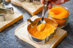 Sprinkling orange sugar with a spoon into a silver pumpkin cutter on a slice of white bread