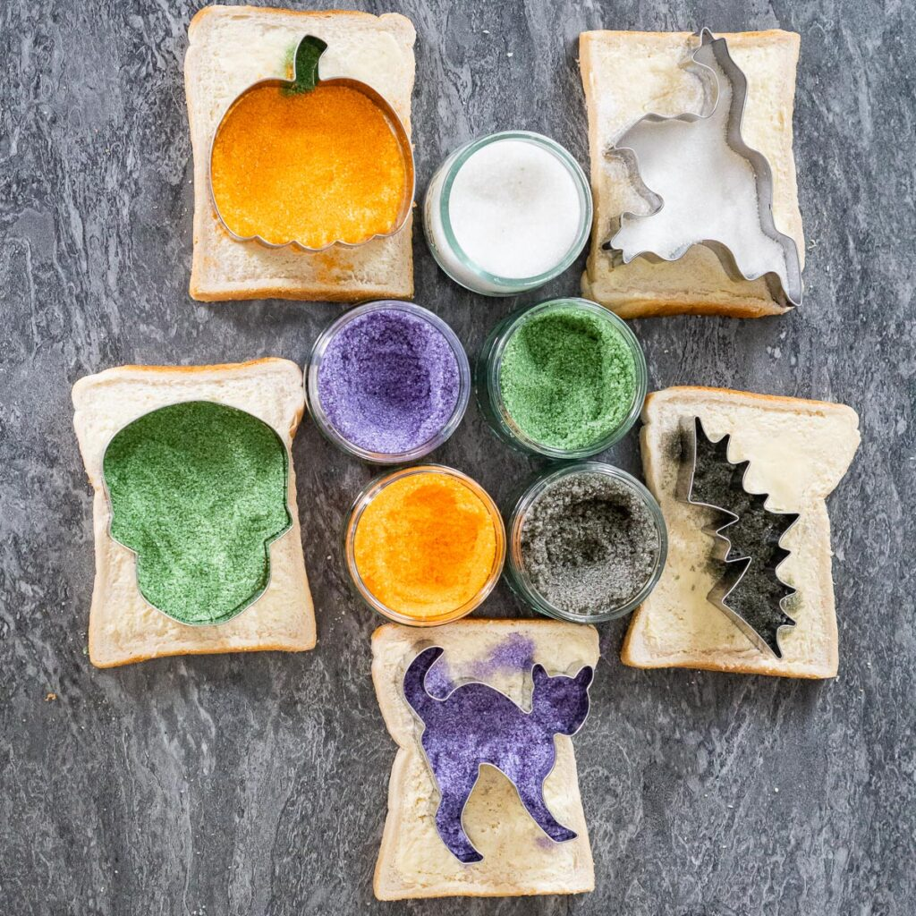 Five slices of buttered bread with each slice having a sugar coated Halloween characters pumpkin, Frankenstein, ghost, bat and cat and five glass ramekins with purple, green ,orange, black and white sugar inside them