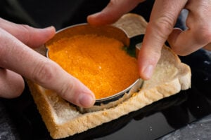 Cutting out a orange sugar pumpkin bread in a slice of buttered bread by hands
