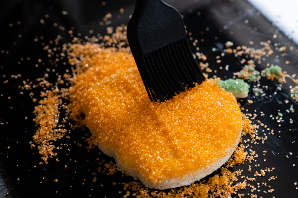Brushing off excess orange sugar with a black rubber brush from the pumpkin cut out