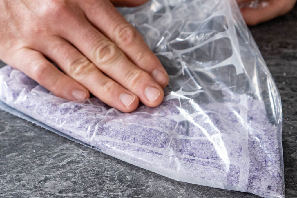 Rubbing purple colouring by hand into the granulated sugar in a clear food bag