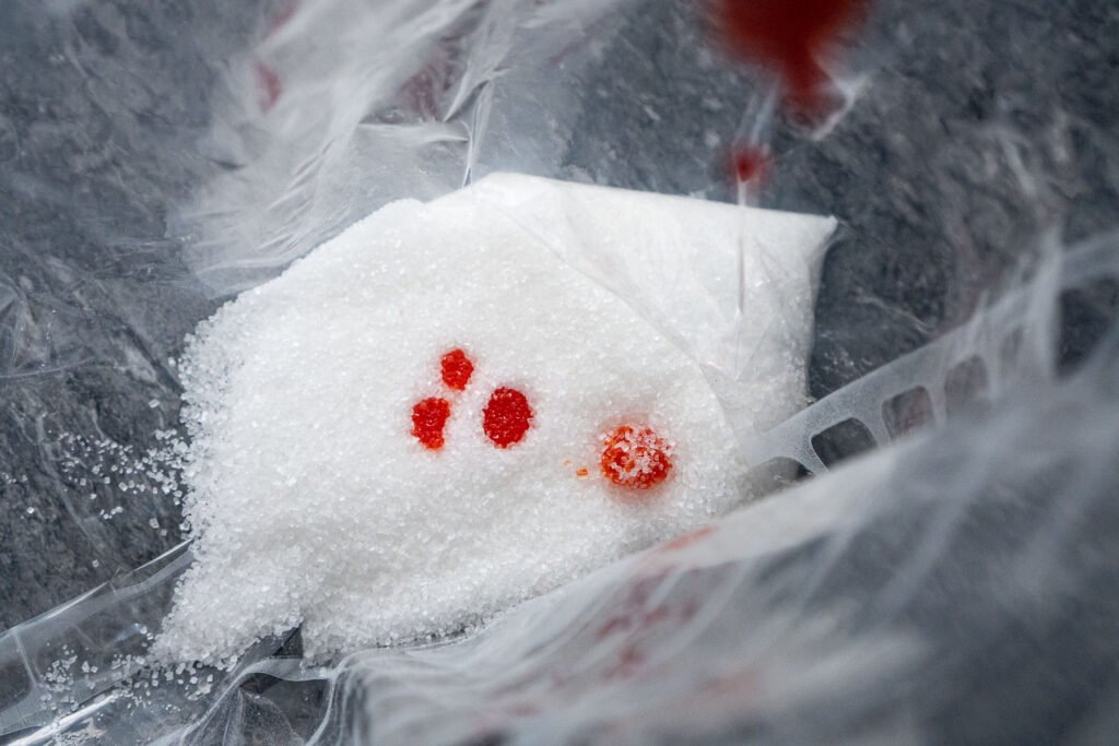 Drops of orange food colouring being added to white sugar in a food bag