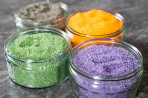 Four glass ramekins with green, orange, black and purple sugar inside them