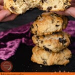 Pin image of holding a rock cake which is broken in half by hand with three rock cakes stacked up in the background