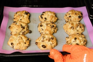 Nine cooked rock cakes being pulled out of the oven.