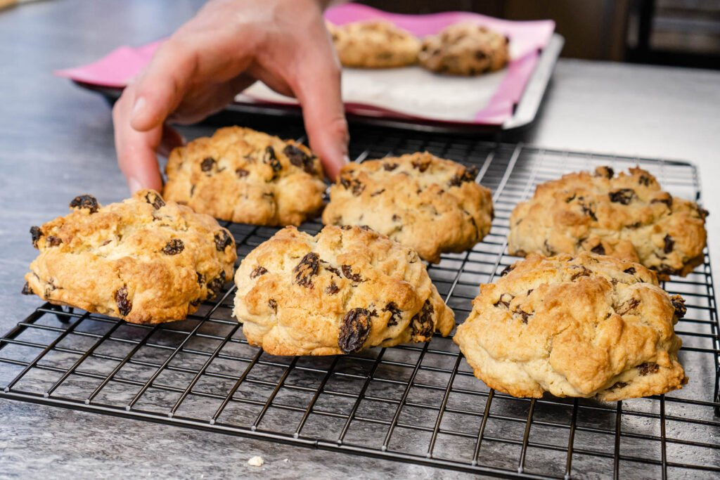 Placing down the cooked rock cakes onto a black metal wire rack to cool off