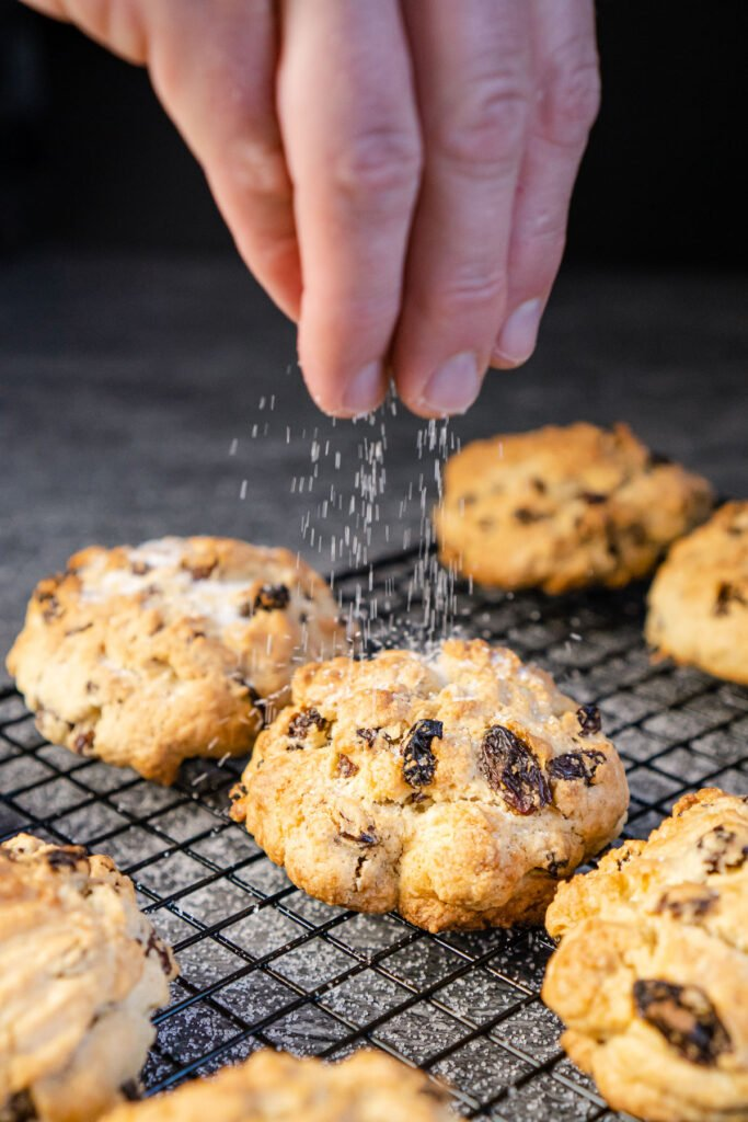 Sprinkling granulated sugar over the top of the rock cakes on a wire rack
