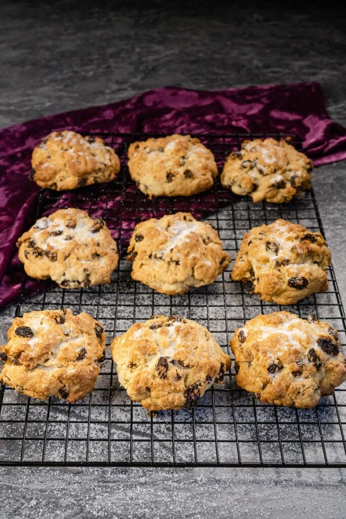 Nine simple rock cakes on a wire rack with sugar sprinkled over the top