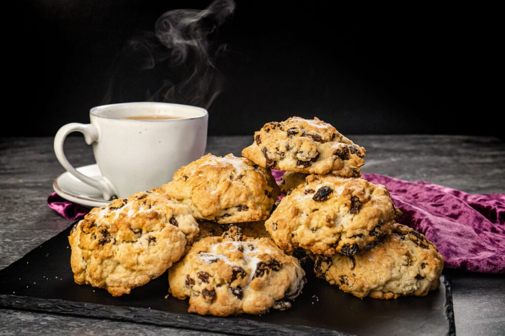 A stack of rock cakes on a slate plate with a cup of tea in the background