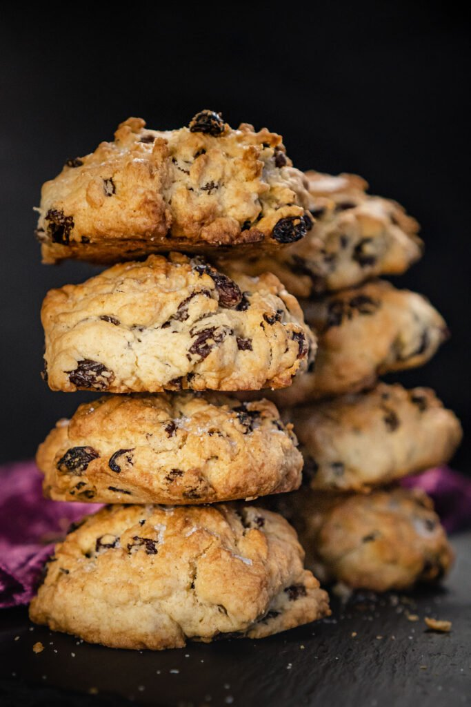 Rock cakes stacked in rows of four on a black slate plate