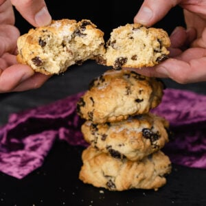Holding a rock cake which is broken in half by hand with three rock cakes stacked up in the background