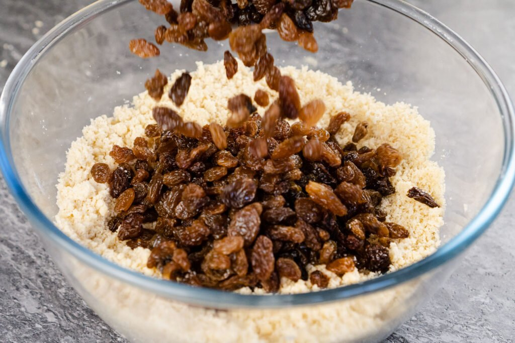 sultanas added into flour and butter cake mix in a glass bowl