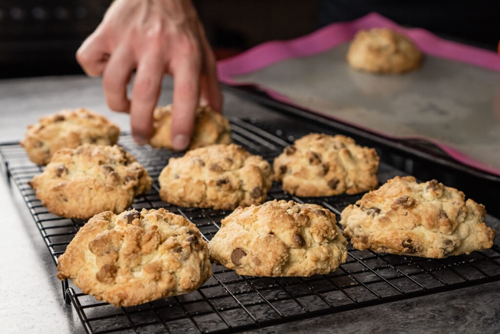 Placing the chocolate chip rock cakes on a black wire rack by hand