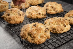Sprinkling granulated sugar over the top of the chocolate rock cakes on a wire rack