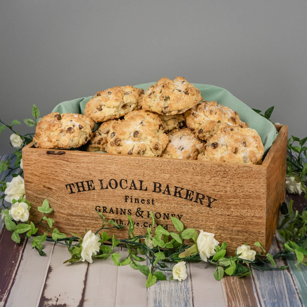 Chocolate rock cakes placed into a wooden local bakery box surrounded with flowers for decoration