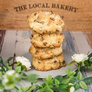Chocolate Rock cakes stacked in rows of four on a grey plate surrounded with white flowers and a local bakery box in the background