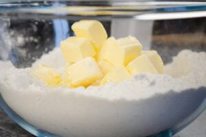 Cubes of butter on top of plain flour in a glass mixing bowl