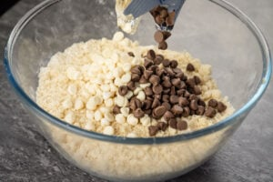 White and chocolate chips being poured on top of the rock cake mixture in a glass bowl
