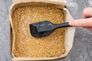 Patting down the flapjack mixture flat with a black spatula