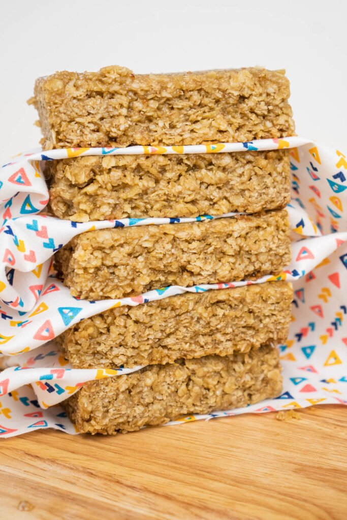 Five Easy Flapjacks Recipe bars stacked up with a white and triangle coloured cloth separating each bar on a wooden board