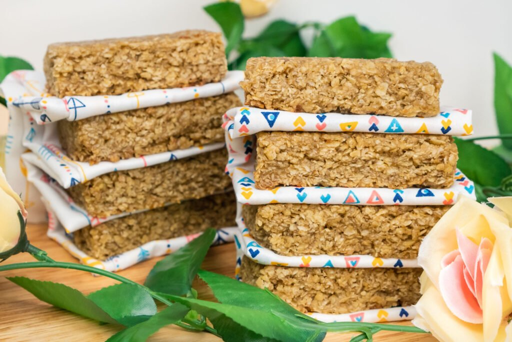 Two stacks of flapjacks with a white and triangle coloured cloth separating each bar on a wooden board surrounded with flowers