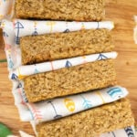 Four oat bars with a white and triangle coloured cloth separating each bar on a wooden board surrounded with flowers