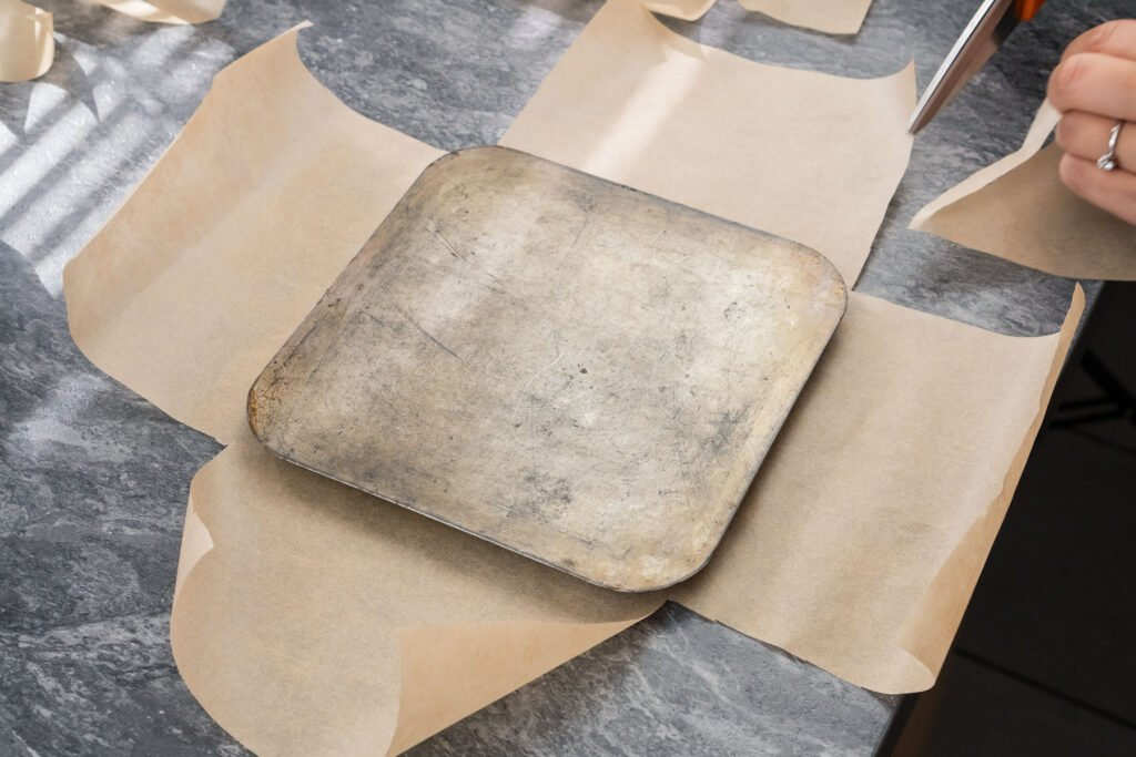 Base of a square baking tin on top of brown parchment paper which is being cut out with scissors to the shape of the tin