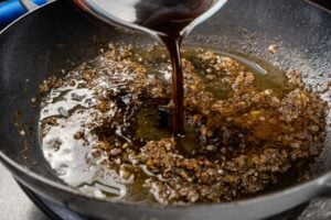 Beef stock pouring into a cast iron pan