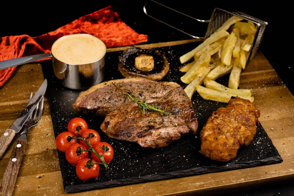 Rump steak served with onion loaf, chips, peppercorn sauce, mushroom and vined tomatoes on a black slate plate seasoned with salt and pepper