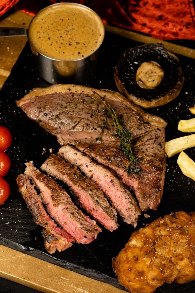 Medium-rare rump steak served with onion loaf, chips, peppercorn sauce, mushroom and vined tomatoes on a black slate plate seasoned with salt and pepper