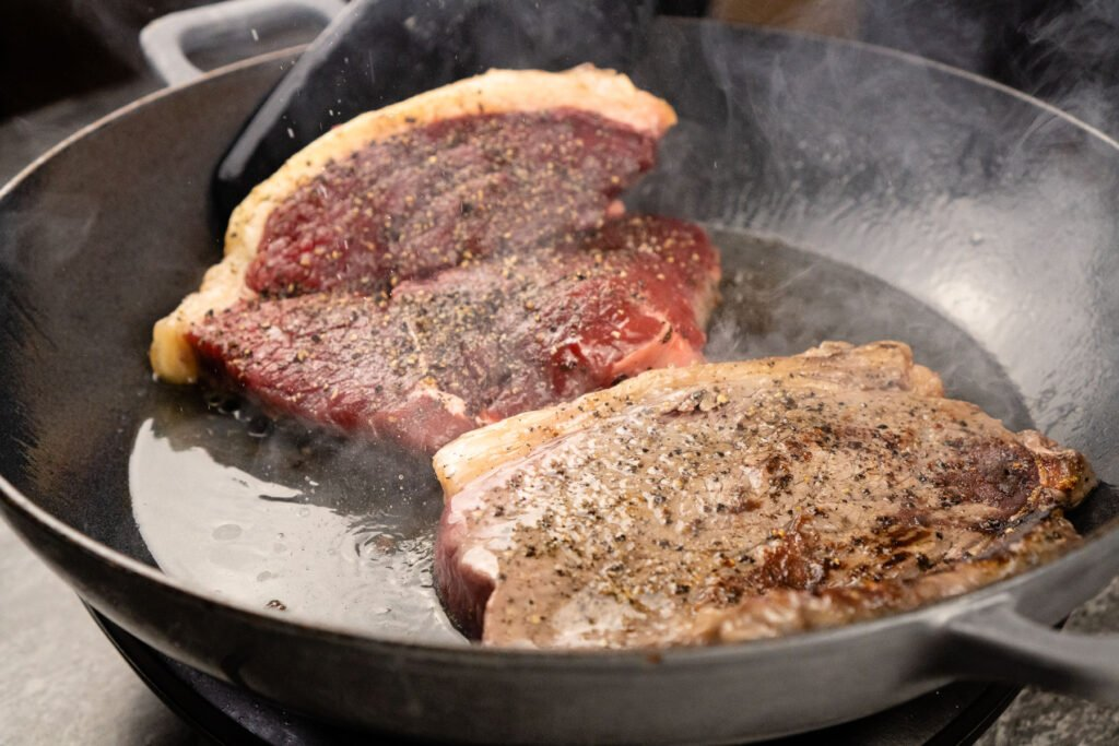 Turning the rump steaks over to cook the other side