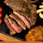Pin image of our Sliced rump steak served with onion loaf, chips, peppercorn sauce, mushroom and vined tomatoes on a black slate plate seasoned with salt and pepper