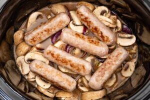Six pork sausages on top of the casserole mixture in a slow cooker pot