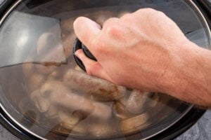 Placing the glass lid on top of the slow cooker pot by hand