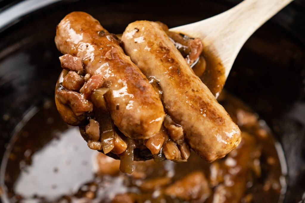 Two sausages with mushrooms and bacon lardons on a wooden spoon