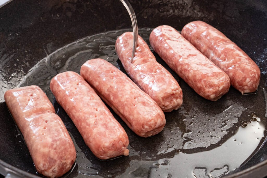 Six pork sausages in a cast iron pan being pricked with a silver fork