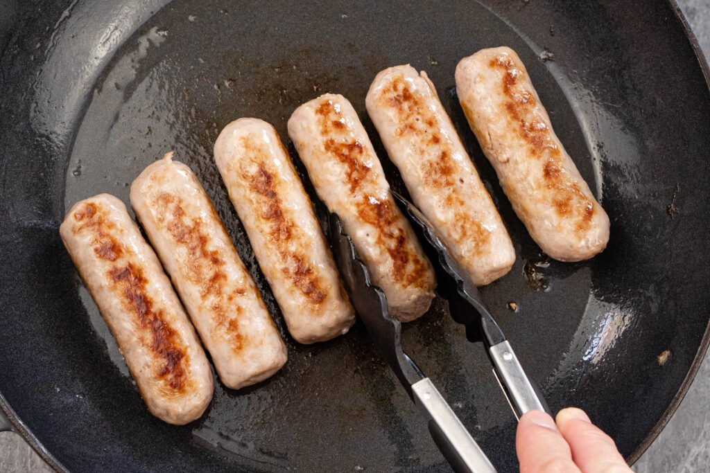 Browning off six sausages in a cast iron pan and turning them over with black and silver tongs