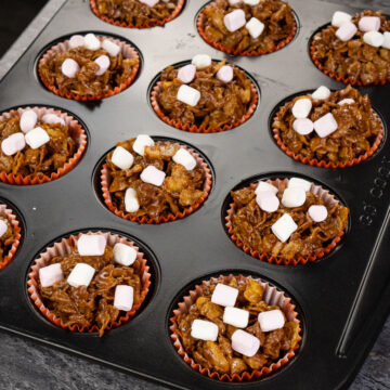 chocolate cornflake cake in orange cupcake cases in a metal cupcake tin with pink and white marshmallows sprinkled over the top