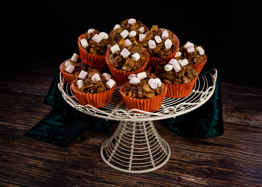 A stack chocolate cornflake cake in orange cupcake cases served a a white metal cake stand with a green cloth around it