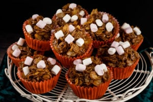 A stack chocolate cornflake cake in orange cupcake cases with marshmallows on top served a a white metal cake stand