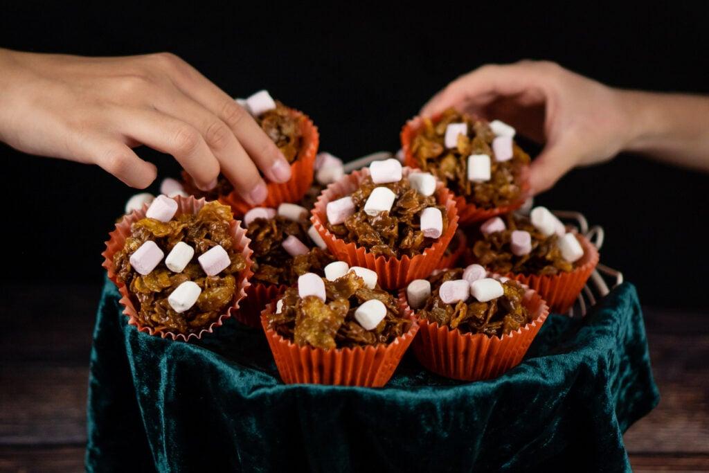 Hands picking up chocolate cornflake cakes