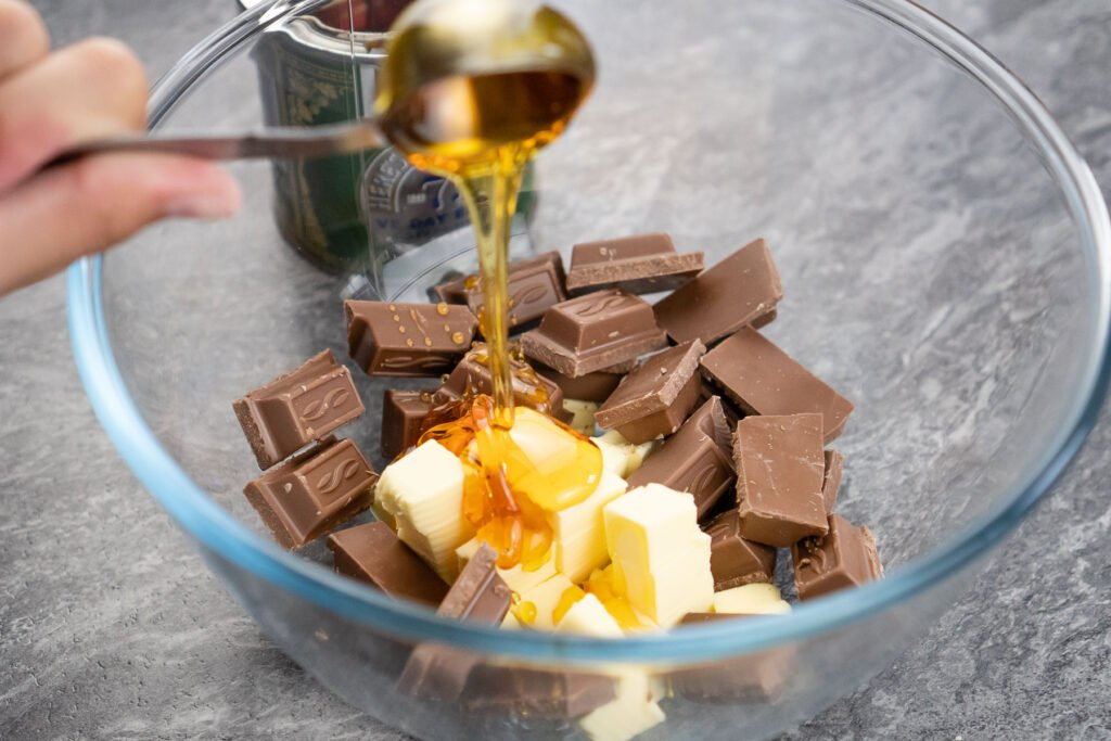 Pouring syrup on top of chunks of milk chocolate and cubed butter in a clear glass mixing bowl