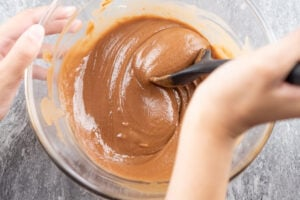 Stirring the chocolate mixture together in a glass bowl with a black rubber spoon