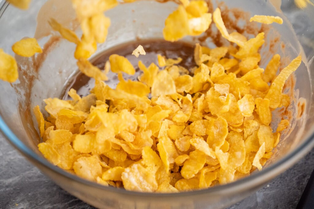 Pouring cornflakes on top of the chocolate mixture in a clear glass bowl