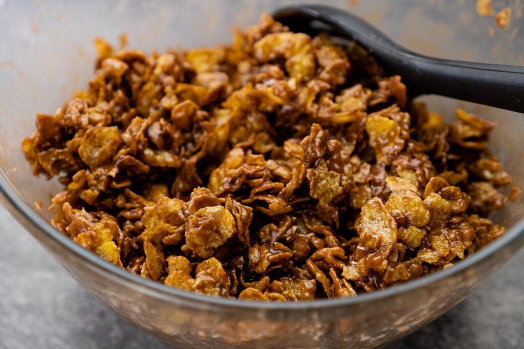 Mixing the chocolate mixture and cornflakes together with a black spoon