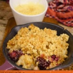 Pin image of our Apple and Blackberry Crumble served in a mini cast iron pan served with custard on the side in a white pot