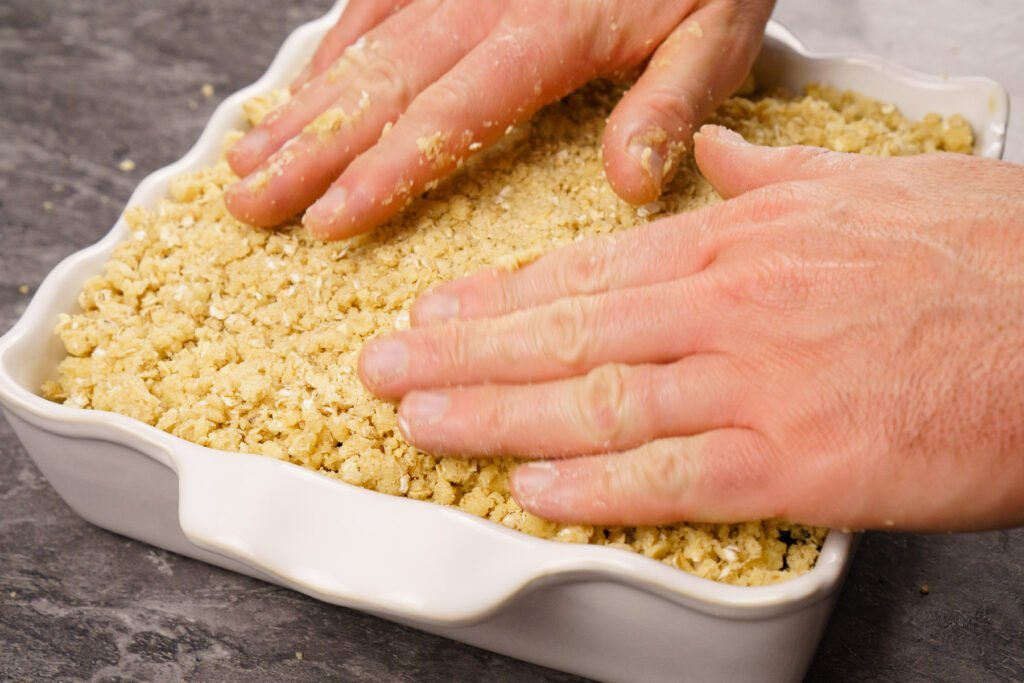 Placing the crumble mix on top of the apples and blackberries by hand in an oven proof dish