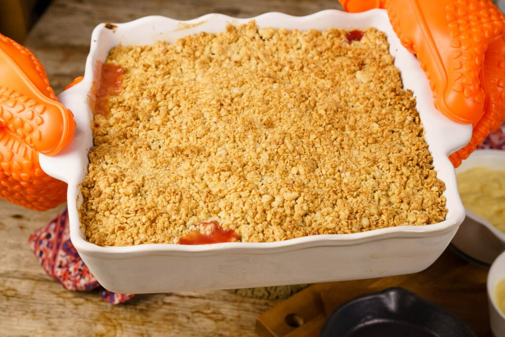 Cooked Apple and Blackberry Crumble being held by hands with orange gloves